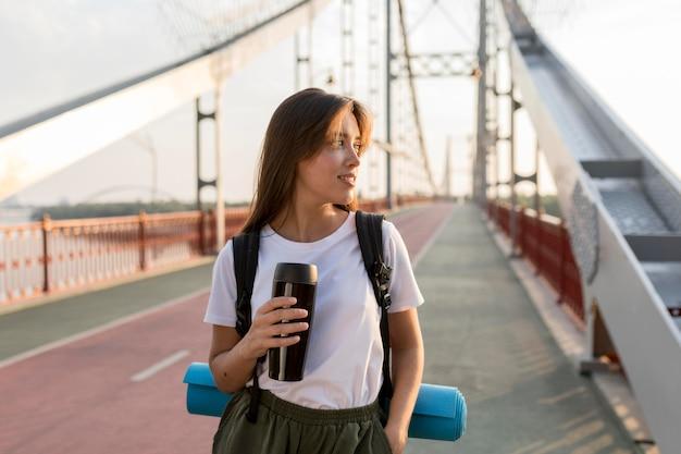 Mulher viajando com mochila posando na ponte enquanto segura a garrafa térmica