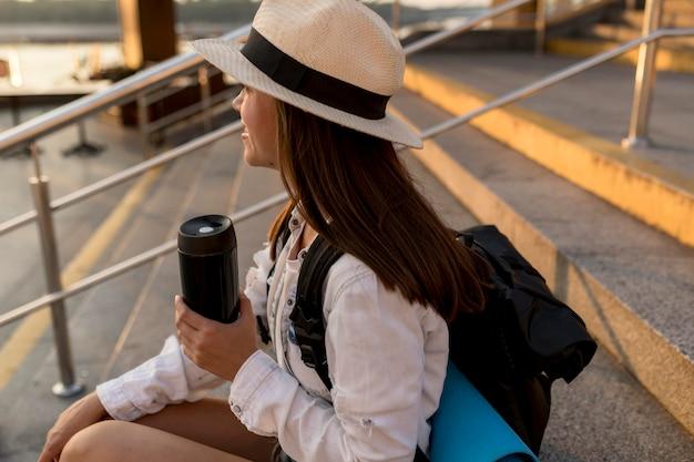 Mulher viajando com mochila segurando uma garrafa térmica