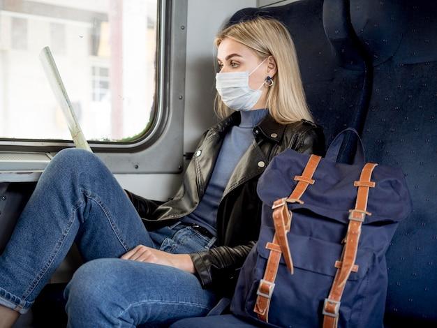 Mulher viajando com trem e usando máscara