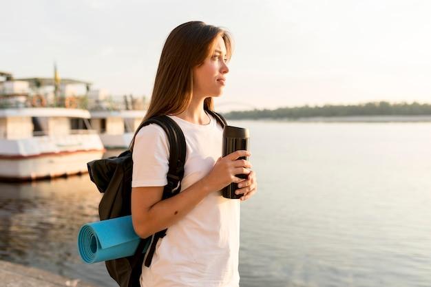 Mulher viajando com uma mochila segurando uma garrafa térmica e admirando o rio
