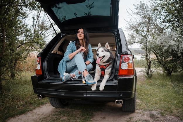 Mulher viajando de carro com seu husky