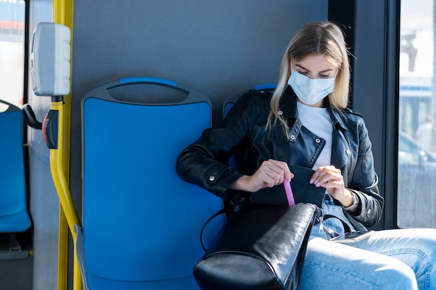 Mulher viajando de ônibus público e usando máscara médica para proteção