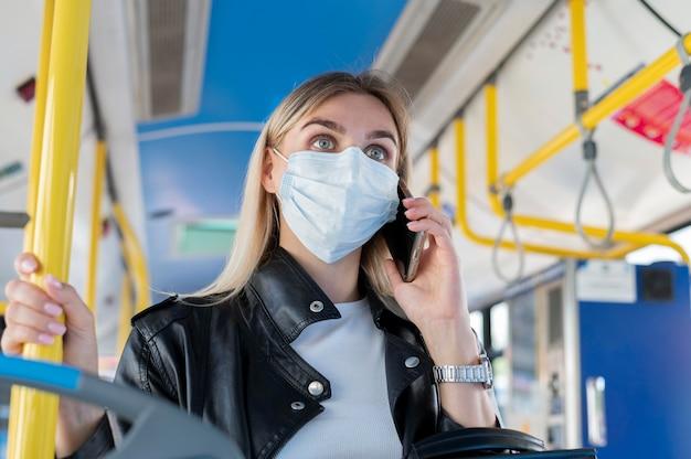 Mulher viajando de ônibus público falando ao telefone enquanto usa máscara médica para proteção