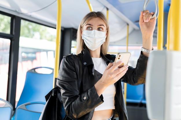 Mulher viajando de ônibus público usando smartphone enquanto usa máscara médica para proteção