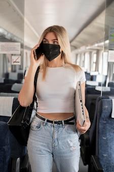 Mulher viajando de trem e falando ao telefone enquanto usa máscara médica
