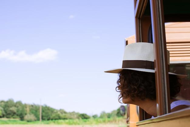 Mulher viajando de trem olhando a janela, vestindo um chapéu sobre férias de verão