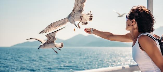 Mulher viajando em ferryboat e alimentando gaivotas