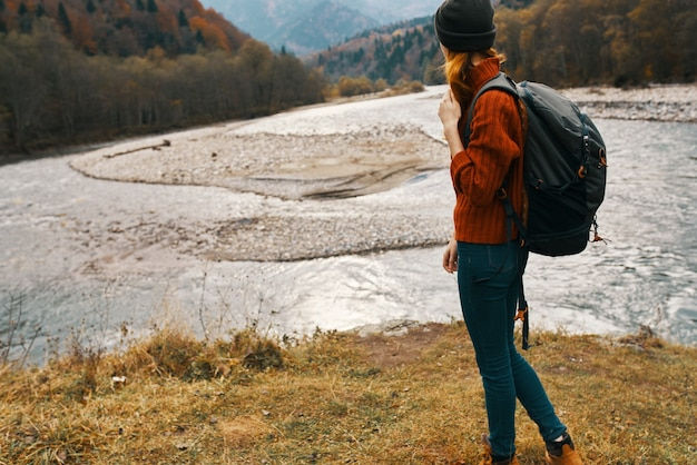Mulher viajando nas montanhas na natureza no outono perto do rio e férias de moletom com chapéu de mochila