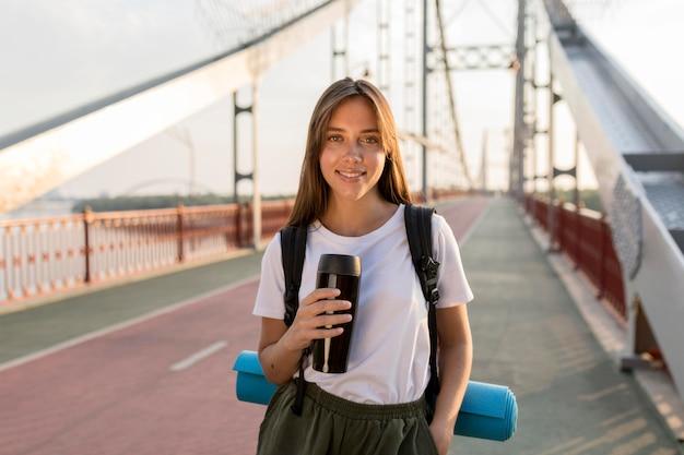 Mulher viajando posando na ponte com garrafa térmica e mochila