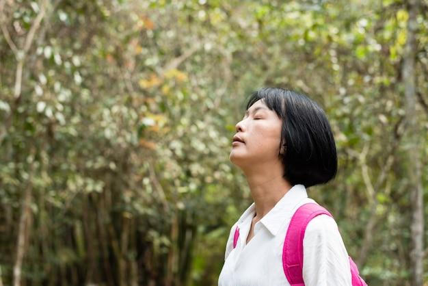 Mulher viajando sente-se à vontade na floresta em taiwan