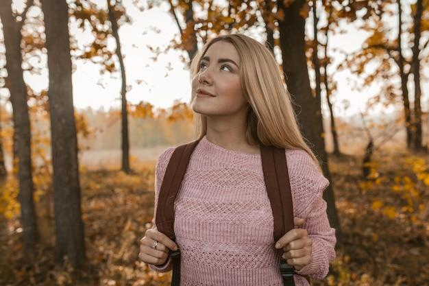 Mulher viajante admira a beleza da floresta de outono