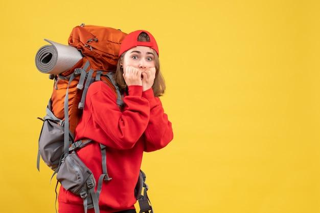 Mulher viajante agitada de vista frontal com mochila vermelha
