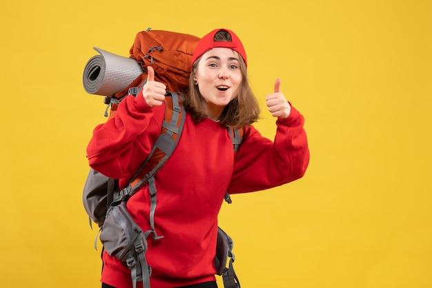 Mulher viajante alegre com mochila fazendo sinal de positivo