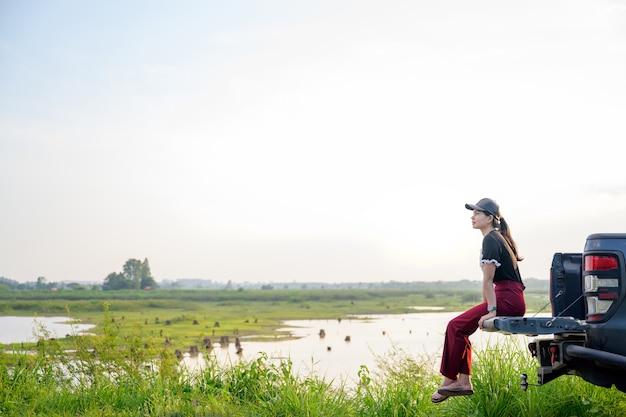 Mulher viajante asiática acampando na parte de trás de um carro com um fundo perto de um lago ou rio em tons vintage mulher jovem feliz viajando em uma estrada rural de verão garota sentada na parte de trás do carro