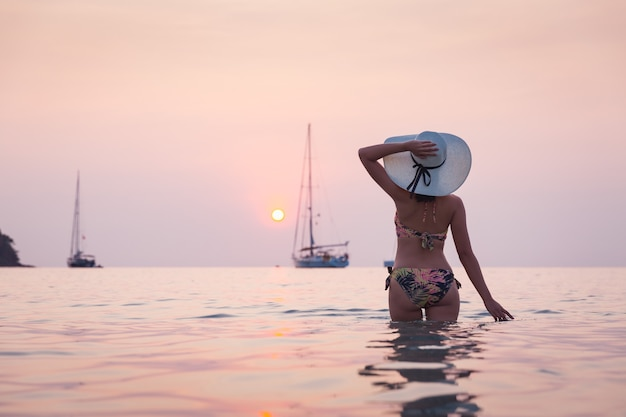 Mulher viajante asiática com biquíni e chapéu relaxando na praia ao pôr do sol em koh kood, tailândia