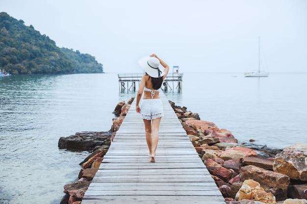 Mulher viajante asiática relaxando em ponte de madeira na praia em koh kood trad tailândia