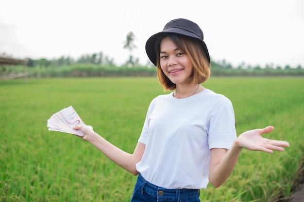 Mulher viajante asiática segurando o dinheiro da nota tailandesa e sorrindo para a paisagem verde