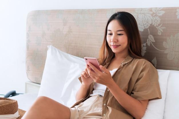 Mulher viajante asiática sentada e usando o celular na cama em um quarto de hotel