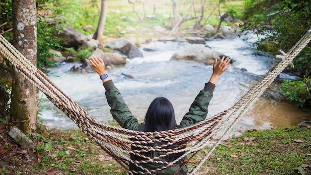 Mulher viajante asiática sentada em rede em hotel resort tropical