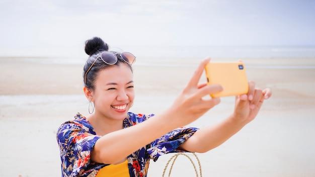Mulher viajante asiática sentar e relaxar na praia à beira-mar