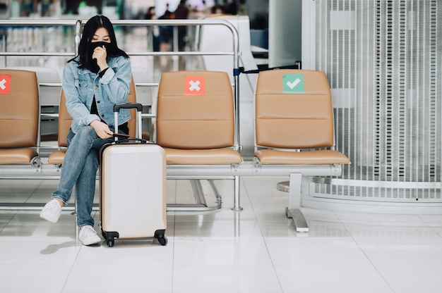 Mulher viajante asiática usando máscara facial, tossindo enquanto está sentada na cadeira de distanciamento social com sua bagagem