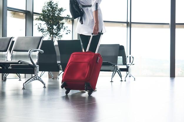 Mulher viajante com bagagem sobe as escadas no saguão do aeroporto ou da estação de trem