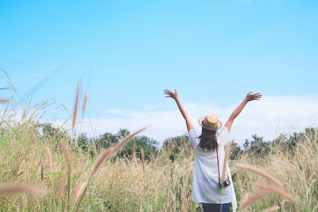 Mulher viajante com câmera empurrar as mãos e respirar no campo de gramíneas e floresta, conceito de viagem wanderlust, espaço para texto, momento épico atmosférico