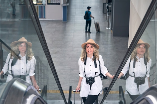 Mulher viajante com câmera sobe a escada rolante no aeroporto