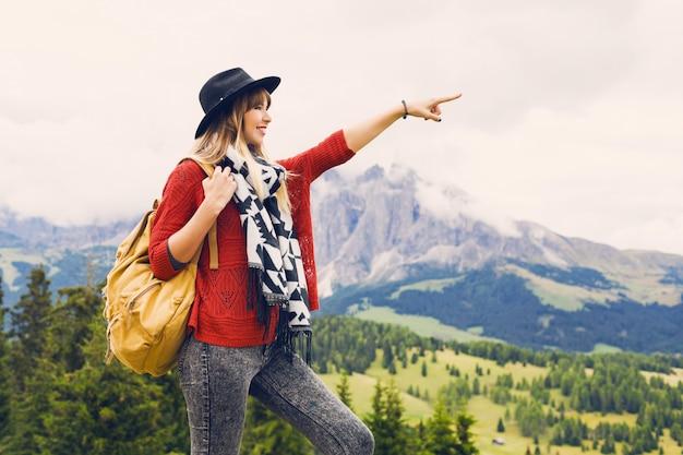 Mulher viajante com chapéu e mochila desfrutando de uma vista incrível da montanha