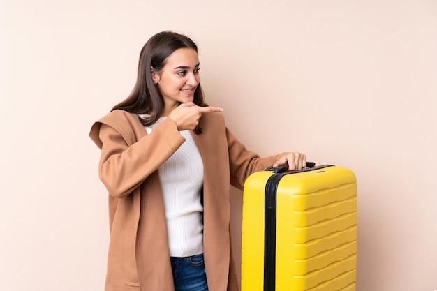 Mulher viajante com mala apontando para o lado para apresentar um produto