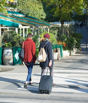 Mulher viajante com mala de viagem ou bagagem andando pelas ruas de paris