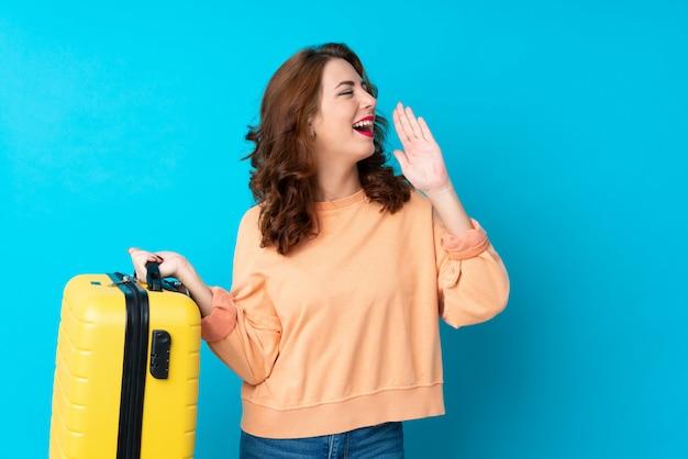 Mulher viajante com mala isolada gritando com a boca aberta