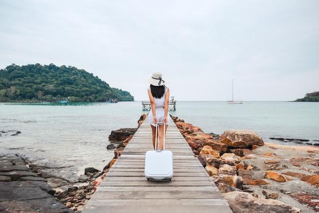 Mulher viajante com mala na praia