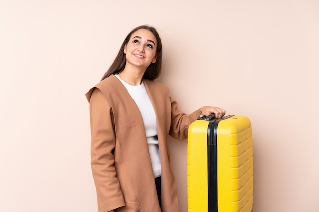 Mulher viajante com mala olhando para cima enquanto sorrindo