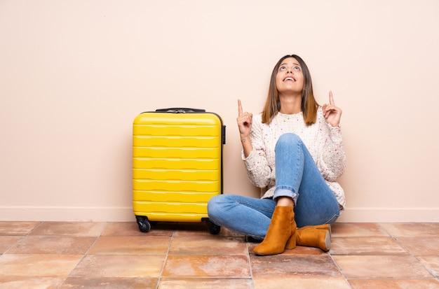 Mulher viajante com mala sentada no chão apontando com o dedo indicador uma ótima idéia
