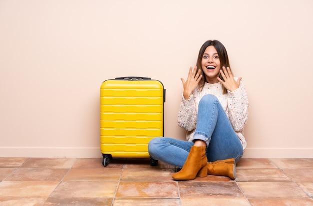 Mulher viajante com mala sentada no chão com expressão facial de surpresa