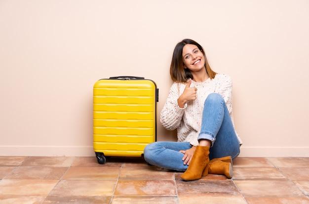 Mulher viajante com mala sentada no chão, dando um polegar para cima gesto