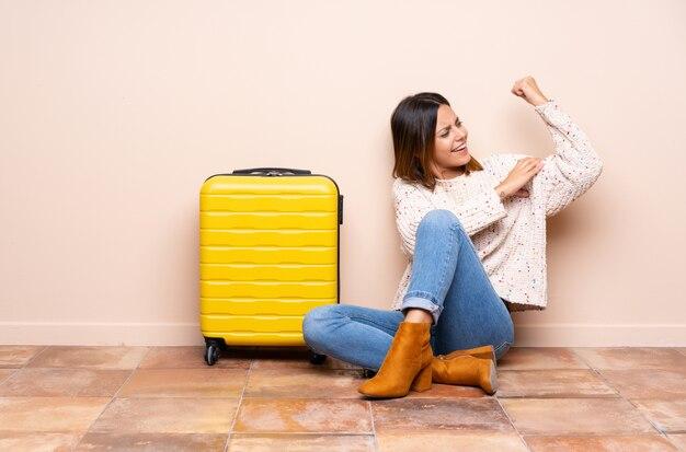 Mulher viajante com mala sentada no chão, fazendo um gesto forte