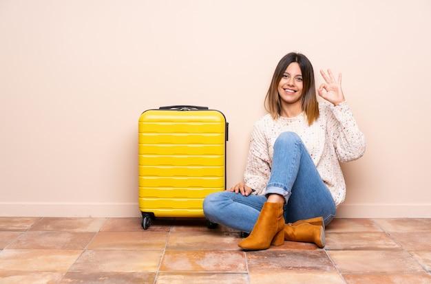 Mulher viajante com mala sentada no chão, mostrando um sinal de ok com os dedos