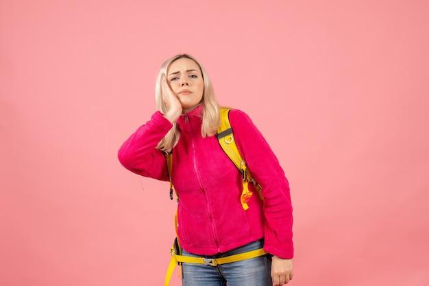 Mulher viajante com mochila amarela colocando a mão na bochecha