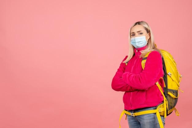 Mulher viajante com mochila amarela e máscara cruzando as mãos