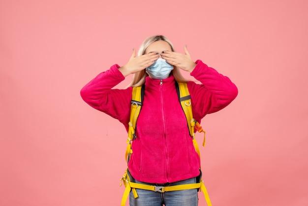 Mulher viajante com mochila amarela e máscara de mãos sobre os olhos