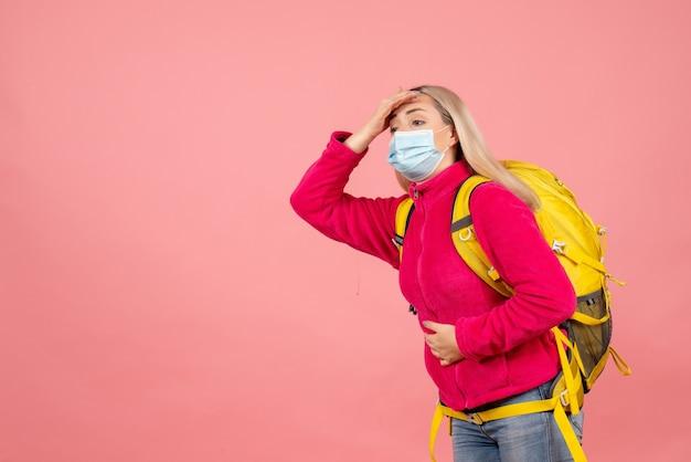 Mulher viajante com mochila amarela e máscara segurando a barriga