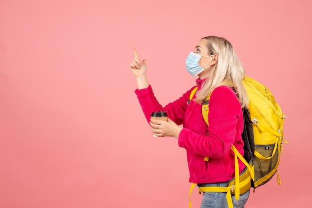 Mulher viajante com mochila amarela e máscara segurando a xícara de café apontando o dedo para cima