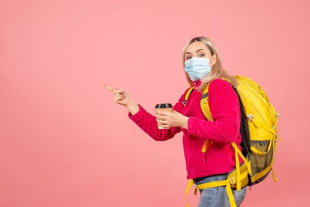 Mulher viajante com mochila amarela e máscara segurando a xícara de café apontando para a esquerda