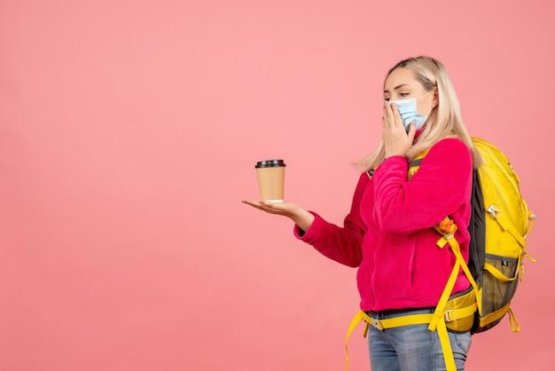 Mulher viajante com mochila amarela e máscara segurando a xícara de café
