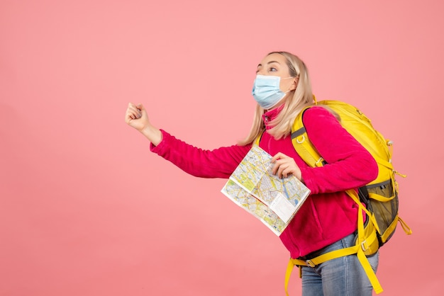 Mulher viajante com mochila amarela e máscara segurando o mapa pedindo carona
