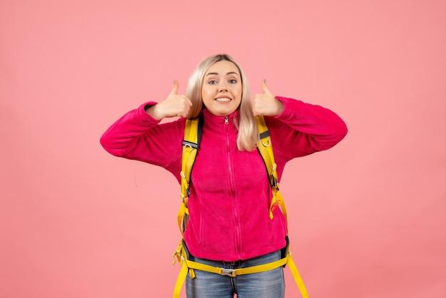 Mulher viajante com mochila amarela fazendo sinal de positivo