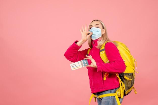 Mulher viajante com mochila amarela segurando bilhete fazendo sinal de beijo de chef