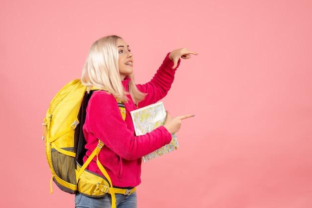 Mulher viajante com mochila amarela segurando o mapa na parede rosa